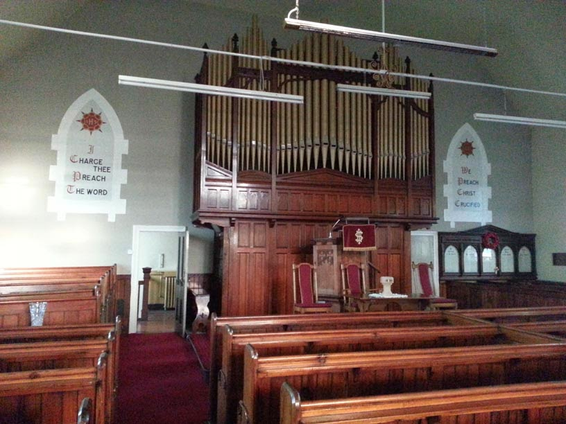 A colour photo of the inside of a church - to the right of the pulpit and organ is a five sectioned wooden panelled structure on the wall.