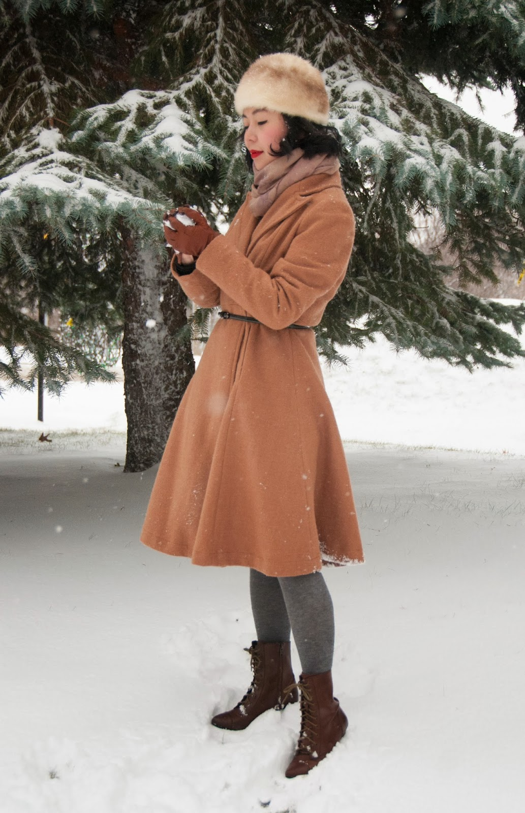 camel flared coat patent belt lace-up booties grey tights fur hat scarf red lips winter fashion