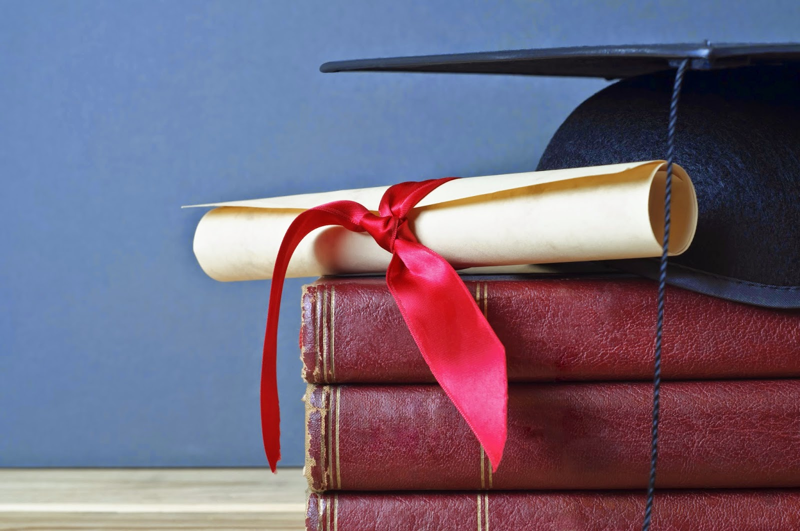 Image of graduation cap stacked on top of books next to diploma