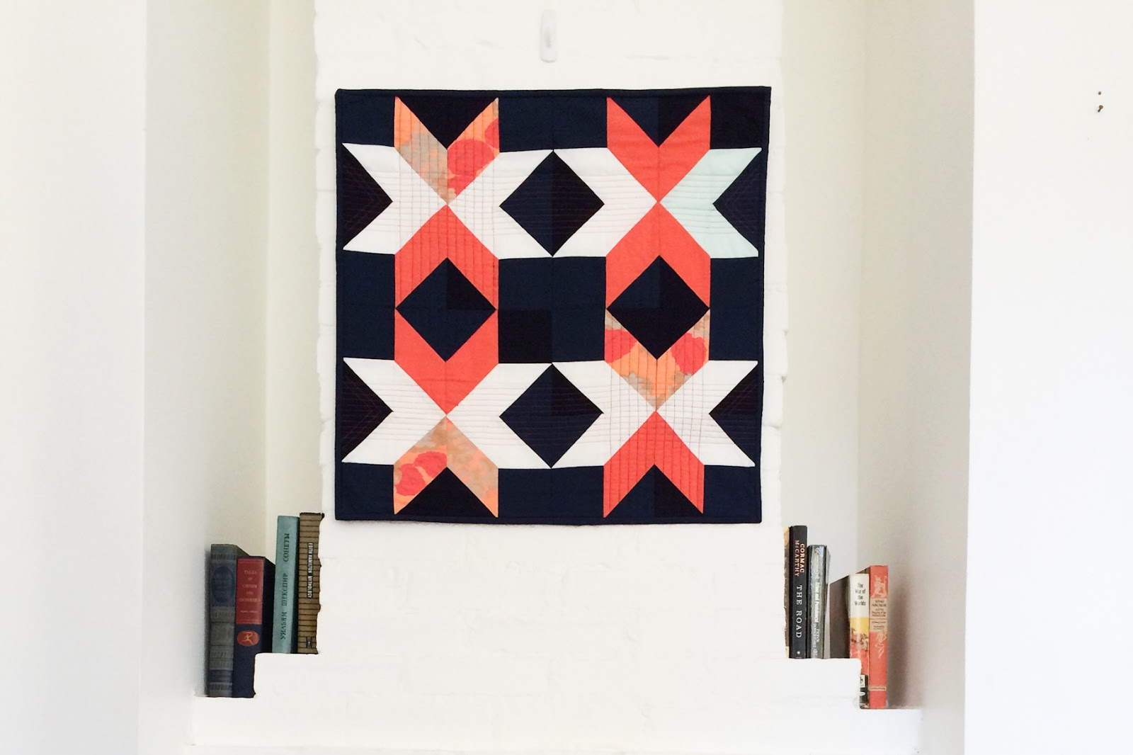 Dark Star coral and navy modern wall quilt living in its Mississippi home   by Lovely and Enough