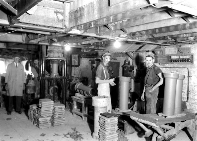 Heathfield Potteries, Newton Abbot. Bovey Tracey ball clays. Great Western Potteries, Heathfield. Pipe making. Clay is fed on the floor above, into the pipe press (on left) and moulded under pressure. The picture shows a pipe partly removed from the press. On removal it is put vertically on a wooden slab and placed on a revolving table (in front of central figure) where, while turning, it is trimmed and has grooves made at both ends with a comb. The pipe is then stocked for drying before firing.
