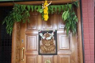house door with marigold flowers and leaves tied