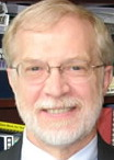 A head shot of Dr. John Crews. He is in his office, standing in front of a bookcase as a backdrop.