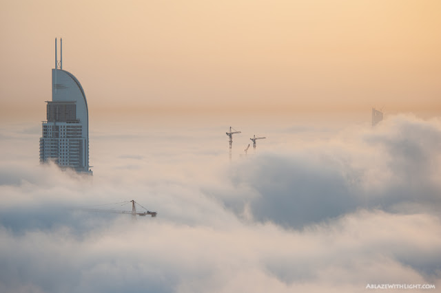 Photo of the building under construction and some tower cranes above the fog