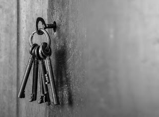 5 metal keys hanging from a ring with one inserted into a door lock to symbolize succeeding as a new manager