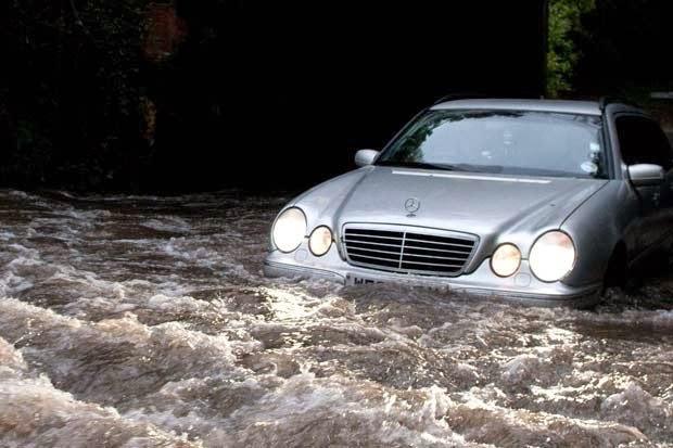 FLOODY HELL: Drivers negotiate a flooded road beneath a railway bridge in Wymondham (Credit: dailystar.co.uk/Alamy)  Click to enlarge.