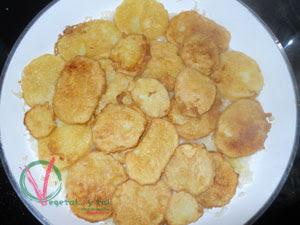 Colocar las patatas fritas sobre el sofrito y cocer con el vino.
