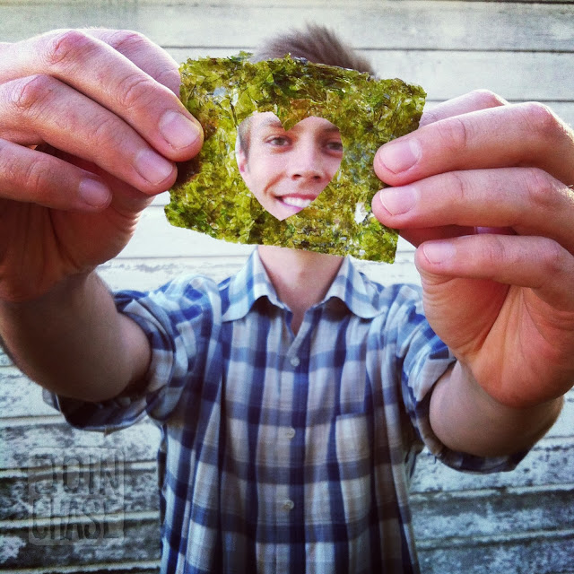 A man holding a sheet of seaweed with a heart cut out of it.
