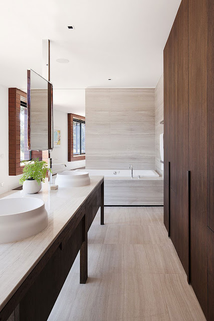 Vanity with White Round Sinks, White Vase with Green and Frameless Mirror