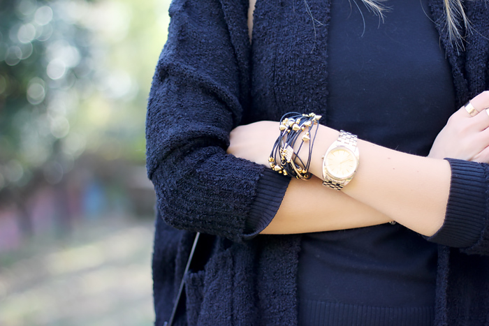 oversized cardigan, layered bracelet, black and gold