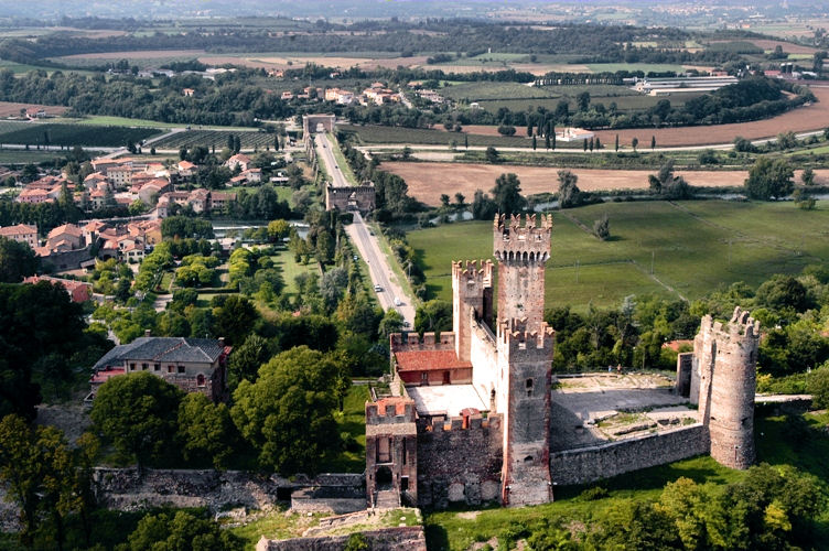 Aerial view of Scaligero Castle in foreground with the Visconti Bridge stretching behind. To the left, the River Mincio and Borghetto. Photo: Courtesy of Tourism.Verona.it.
