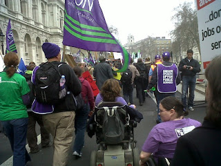 The backs of people marching along Whitehall, including Lou and me