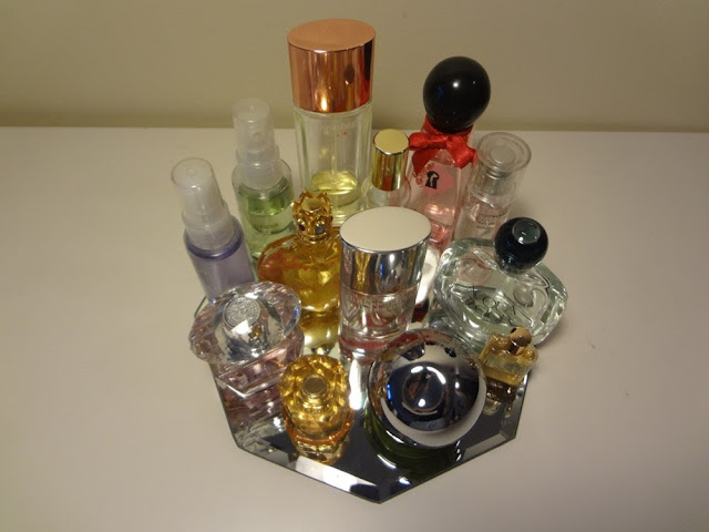displaying perfume bottles on a glass mirror tray
