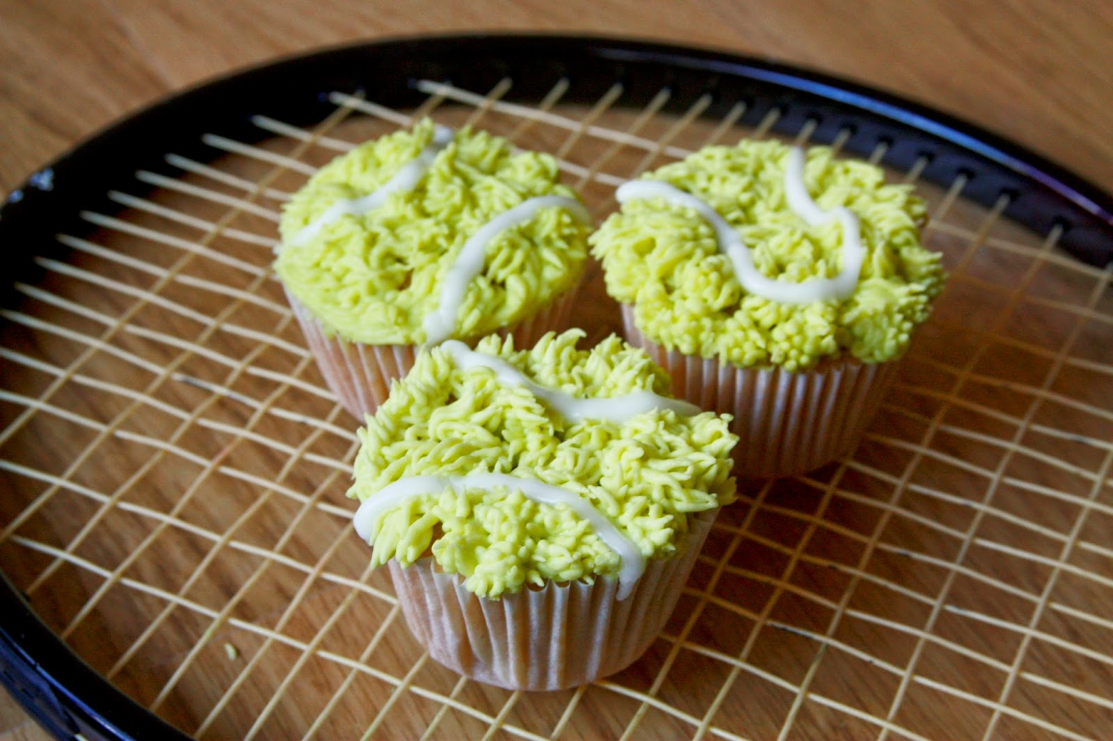 3 Rhubarb and custard flavoured cupcakes iced to look like tennis balls