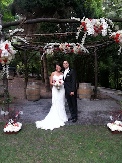 The bride and groom stand under the trellis at JM Cellars - Photo by Patricia Stimac, Seattle Wedding Officiant