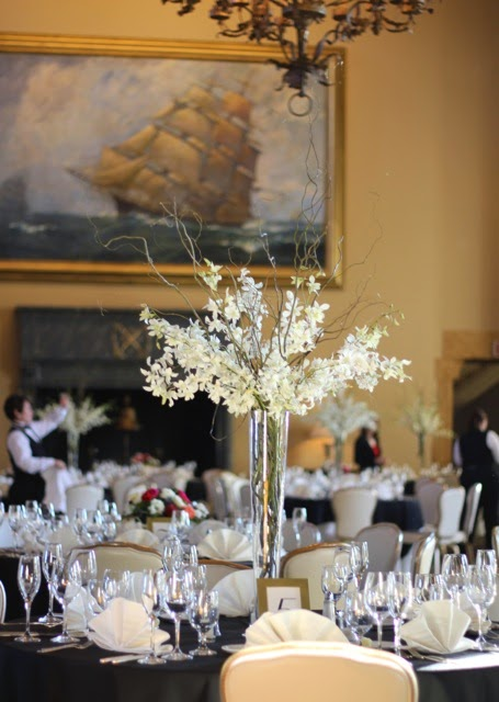 "Elevated Centerpiece by Sweet Pea Floral Design Grosse Pointe Ann Arbor featuring extra long white Hawaiian dendrobium orchids and curly willow in a 24"" clear vase at the Grosse Pointe Yacht Club"