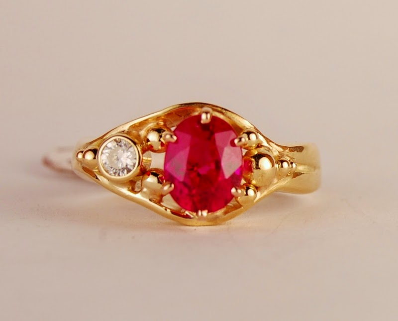 Oval red ruby in a prong setting with a bezel set diamond in a ring