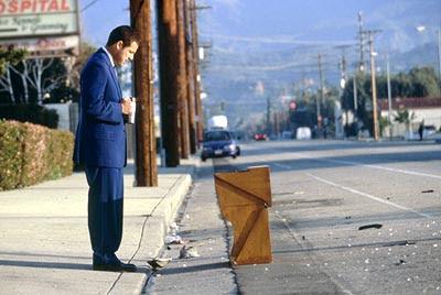 Barry Egan, con una taza de café, mira un mueble destruido.