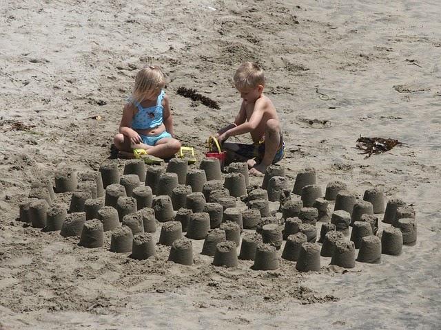 anak kecil asyik bermain pasir di pantai