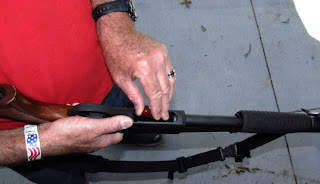 Shotgun supported with hand and armpit.