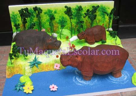 tres hipopotamo en su habitat, unos en tierra y otros en el agua
