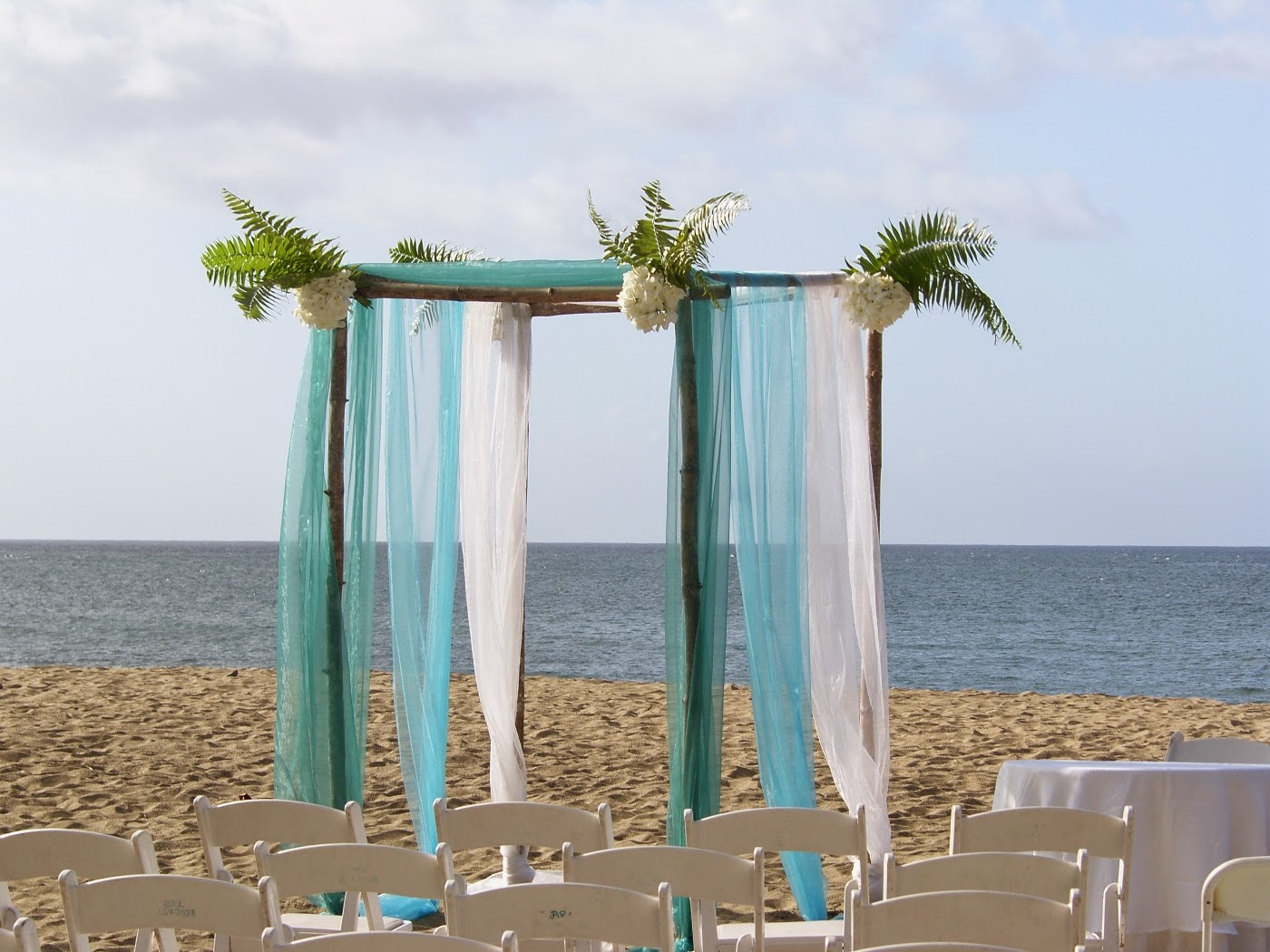 beach wedding arch with green, blue & white pastel colors