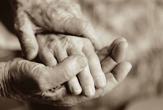 old hands, two male hands gently holding one female hand