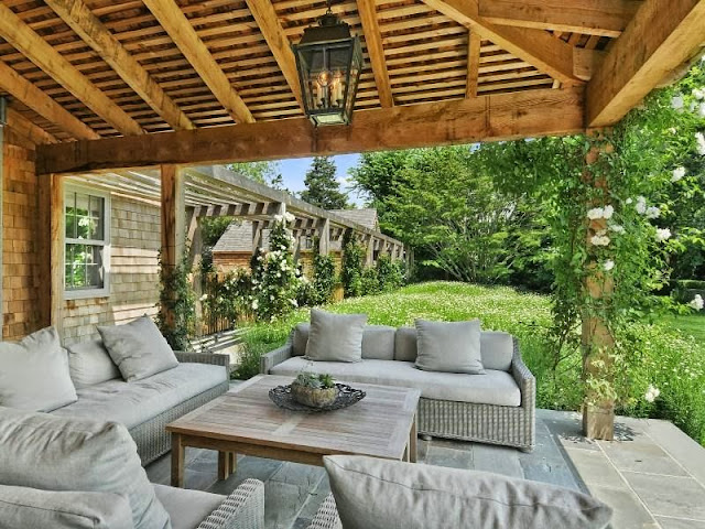 Patio of a house an East Hampton compound with grey sofas, wood table, a lantern light and a gorgeous yard