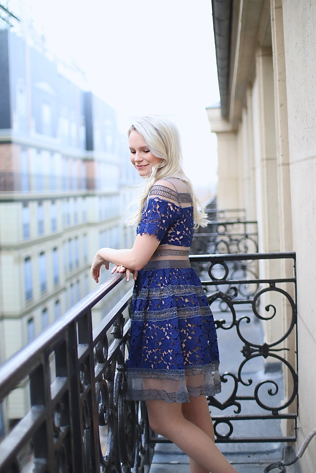 a blonde women wearing a royal blue lace dress looks over a balcony in paris