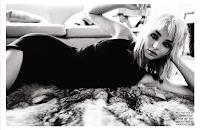 Miranda Kerr in a black dress posing on the floor