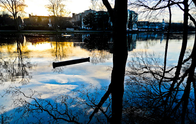 An Evening in York, UK : Posted by Vibha Malhotra on www.travellingcamera.com : When we went to York in winters this year, the last thing we expected to see was a flooded River Ouse. Yet that was the first thing we saw. The long bar in the middle of water in the first photo is actually the top of a wooden bench placed on the side of the river. It would have been interesting to sit on it at this time.The weather was cold and days were short so we decided to start early. We were hoping to see everything in the city by 6 PM because we had a train to catch shortly after that. But we were wrong. We were free by 3:00 PM owing to two things mostly - York being a very small city and our reluctance to chip out money to see anything really.We chanced upon the Yorkshire Museum Gardens where we found the ruins of St. Mary's Abbey at around 3:30 PM and that was to consume the rest of the time of our trip. The Gardens are situated on the banks of the river Ouse and has a cemetary and chapel and also houses the City Art Galery at one end.The ruins in this Garden date back to the 13th century when an extensive rebuilding programme was undertaken and completed. Not much is left of it though. During the day, the lush garden around the ruins make is look very attractive and alive in spite of the age of the buildings.Ruins of the St. Mary's Abbey Church. Walking ahead are my friends Hannah and Kelsey. I love ruins and ancient historical places. There is a mystery around these which only years and years of history can create.Looking at the ruins now, it is very difficult to believe that St. Mary's was once the largest and richest Benedictine establishment in the north of England and St. Mary's Abbey was the largest landholder. A very shocking reminder indeed of the fact that nothing lasts forever.The ruinned Abbey Church and the leafless trees with the setting sun in the backdrop make this place look even more sinister than it actually is. When you are with your friends, the place is ch