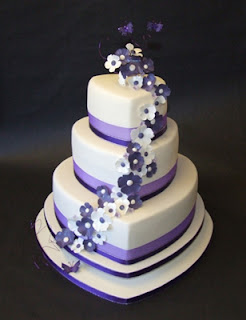 Three Tier Heart Wedding Cake Decorated with Purple & White Flowers