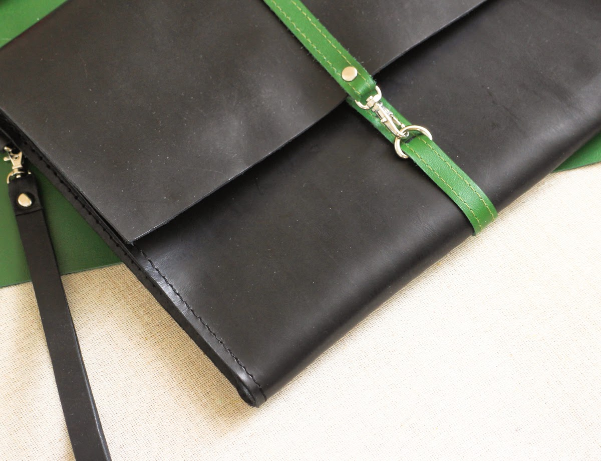 На черном кожаном клатче застежка в виде кожаной зеленой полосы с карабином