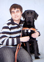 A young man in a black and white striped shirt has his arms wrapped around a black Lab that is wearing a brown Leader Dog harness. Both are sitting down.