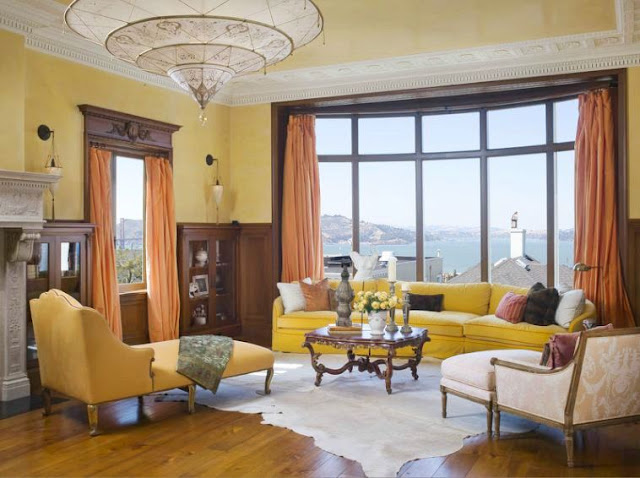 Sitting area in a san francisco mansion's master bedroom with yellow walls, a yellow sectional sofa, two armchairs with ottomans, wide wood paneled floor, animal hide rug, a wood coffee table, moulded ceiling, a fireplace and a large window with a view of the ocean. This window has floor length coral curtains