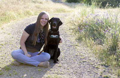 Kylie sits smiling on a dirt road with her arm around a black Lab guide dog puppy.