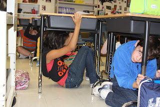 Photo of students participating in emergency drill, sheltering under their school desks.