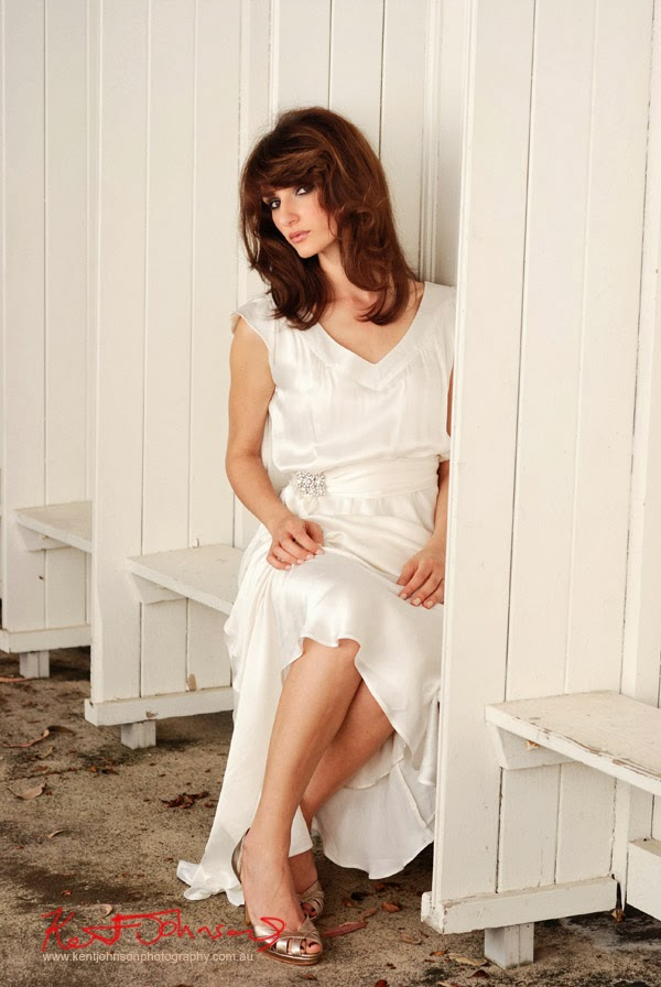 Seated shot, old white timber walls, white satin wedding dress. Photographed by Kent Johnson.
