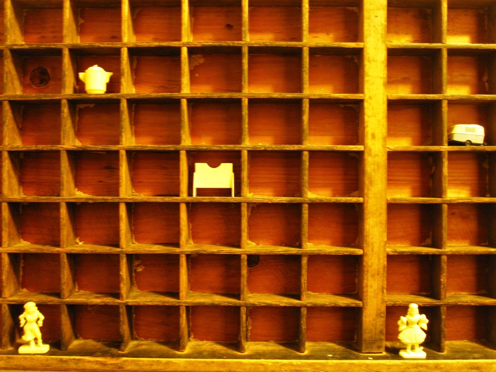 Vintage printer's tray with five cream-coloured miniatures displayed inside.