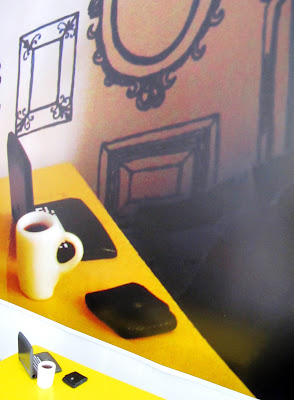 Yellow dolls' house miniature table with laptop and mug of coffee on it, in front of a blown-up photo of the same items in a dolls' house scene.