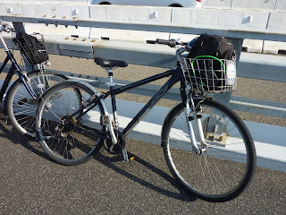 Bicycles hired for the Shimanami Kaido bikeway from a bike terminal in Onomichi. 21 Speed bike with a backet in the front.