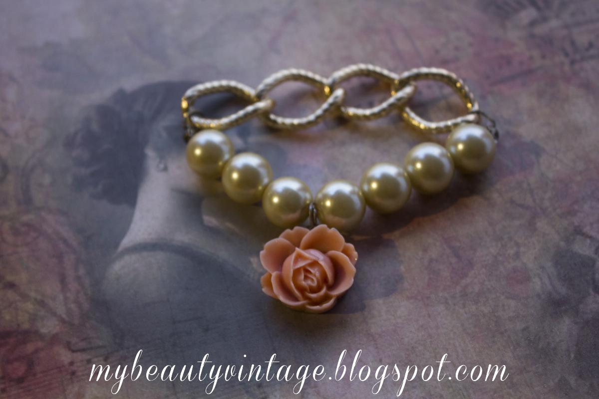 Esta pulsera de bisutería está realizada en cadena tipo eslabón grande dorado y perlas grandes en color ligeramente dorado, con detalle de flor vintage.