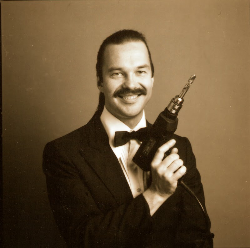 Arthur Jarvinen publicity head shot - smiling, wearing a tux and holding an electric drill