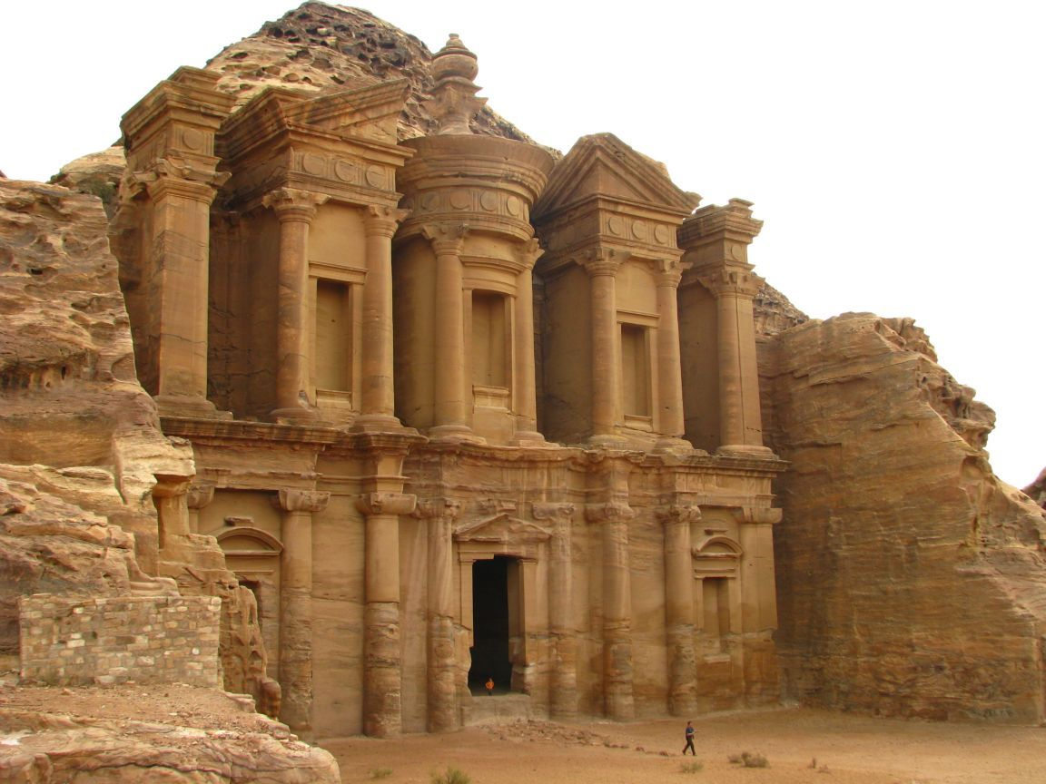 """petra jordan Of the 800 carved tombs in petra, the kazneh is the most famous its name kazneh means """"treasure"""" and comes from the bedouin belief that the pharaoh chasing the israelites hid his treasure in the urn at the top of the kazneh."""