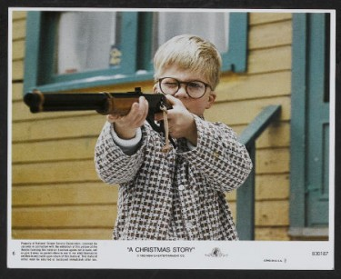 Lobby card of Ralphie aiming his BB gun in A Christmas Story 1983 movieloversreviews.blogspot.com