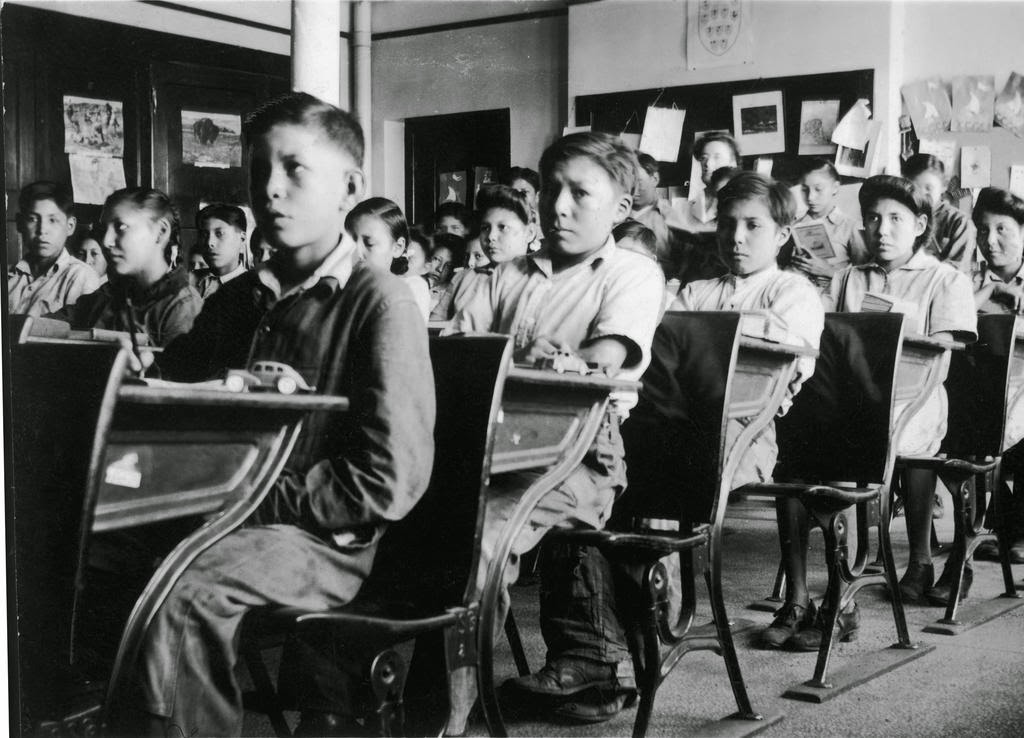 Indigenous children sitting in a classroom at the Old Sun Indian Residential School, 100 Years of Loss Website.
