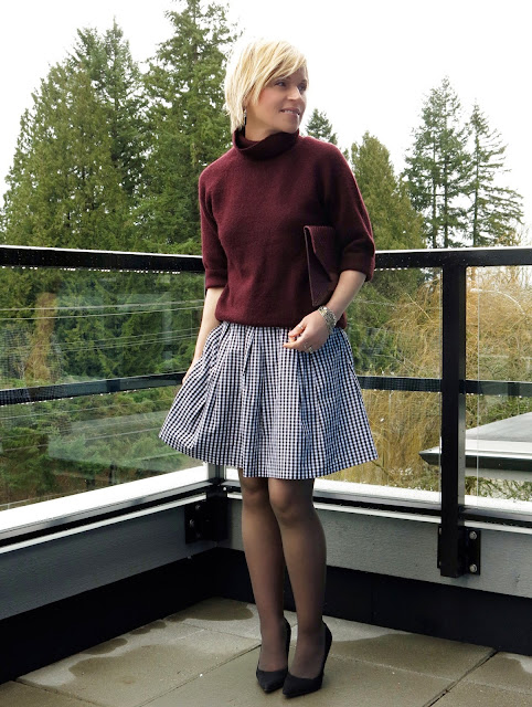 styling a maroon turtleneck with a gingham skirt, black suede pumps, and an envelope clutch