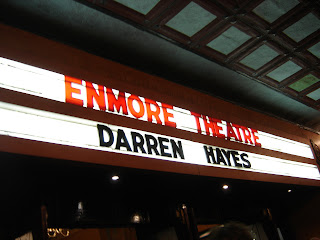 A theatre sign that says Enmore Theatre Darren Hayes above a brass and glass art deco door