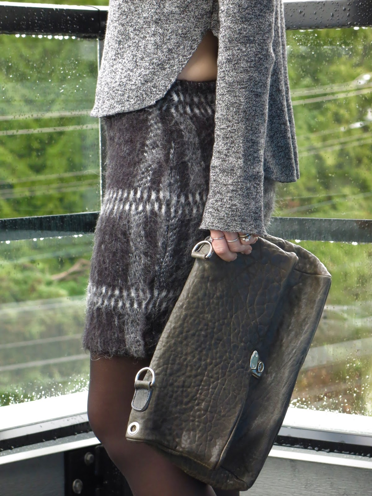 grey marled sweater, plaid mohair skirt, black tights, and pebble-textured bag
