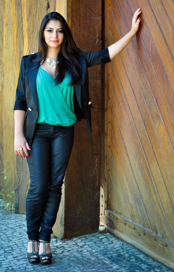 Look com blusa verde esmeralda, maxi colar, blazer preto e sandália de glitter